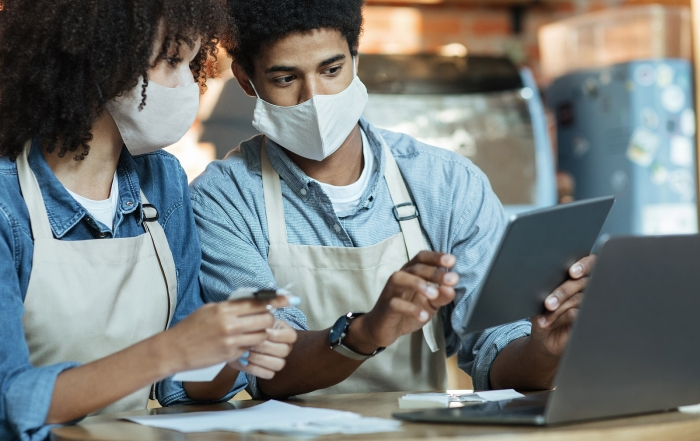 Small business owners at social distancing of covid quarantine. Busy african american couple in aprons and protective masks work with laptop and tablet to attract clients in trendy cafe or restaurant