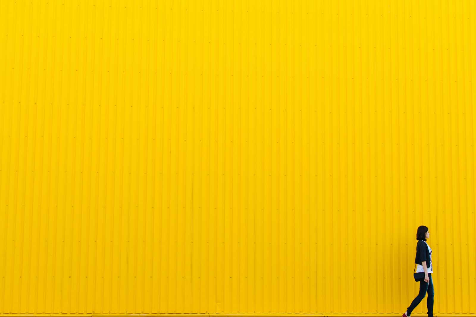 woman walking in frnt of a yellow wall